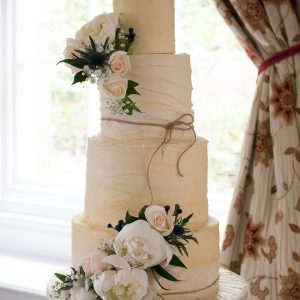 Buttercream Naked Wedding Cake with a double cascade of fresh flowers and personal Mr & Mrs Cake Topper